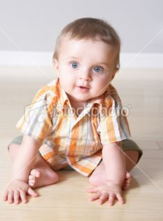 Closeup of an cute little child sitting on floor  Stock Photo